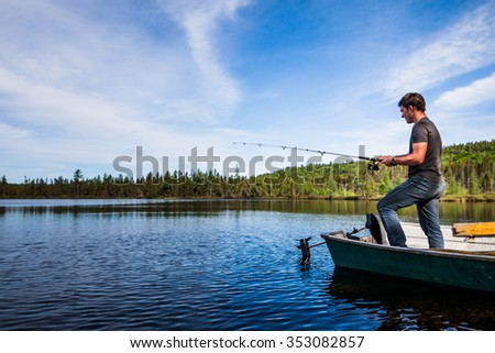 Young Adult Fishing trout from a deck in a calm Lake during the morning