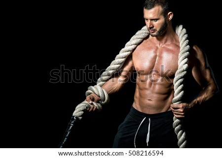 Young adult fit man holding heavy rope around his neck while posing in front of black background.