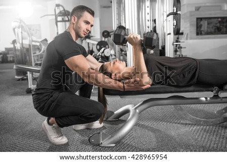 Young adult fitness couple. Woman doing chest and shoulder dumbbell  press on bench with personal coach assisting her and giving instructions. - stock photo