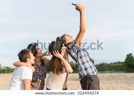 Young adult friends taking selfies with tablet and having fun outdoors - stock photo