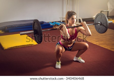 Young adult girl doing heavy duty  squats in gym with barbell - stock photo