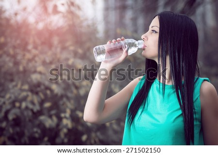 Young adult girl drinking water from bottle in park.