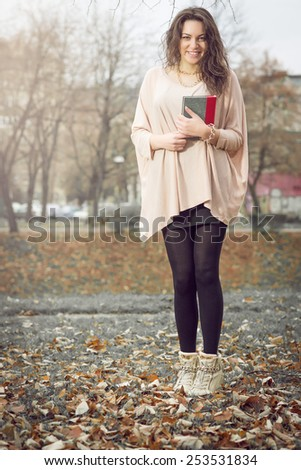 Young adult girl holding a book in park wearing scarf.