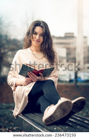 Young adult girl sitting in park and reading a book. - stock photo