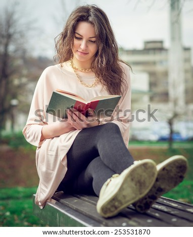 Young adult girl sitting in park and reading a book.