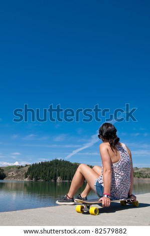 Young adult girl sitting on her long board looking out over a lake on a sunny summer day - stock photo