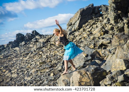 young adult girl to hold balance on peak of mountain against blue heaven with clouds. Woman wear blue gymnastic skirt. moment before the fall on the rocks - stock photo
