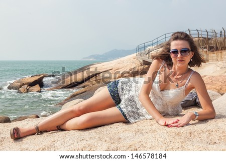 Young adult girl wearing sunglasses when laying on the rock Cheng Chau, Hong-Kong, China