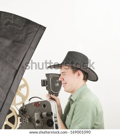 Young adult handsome caucasian male videographer holding a videography old retro style camera on gray background and light box White and black film  - stock photo