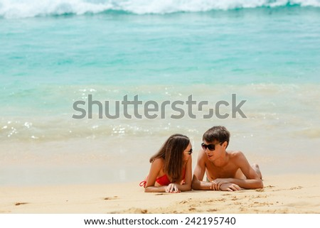 young adult happy couple in sunglasses lying on the beach - stock photo