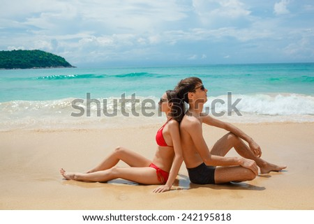 young adult happy couple in sunglasses sitting on the beach