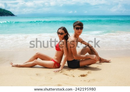 young adult happy couple in sunglasses sitting on the beach - stock photo
