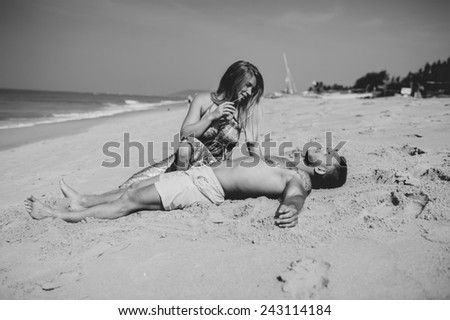 young adult happy couple  sitting on the beach - stock photo