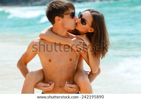 young adult happy kissing couple in sunglasses on the beach - stock photo