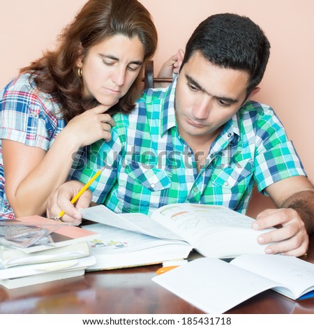 Young adult hispanic couple studying at home - stock photo