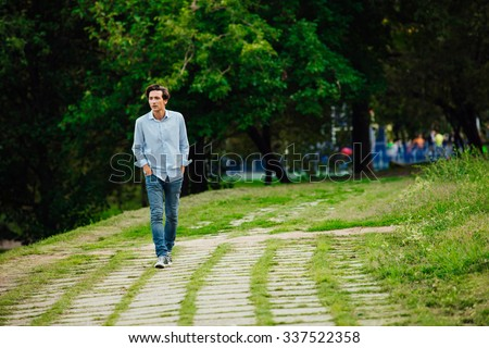 young adult in blue shirt and jeans walking alone in park - stock photo