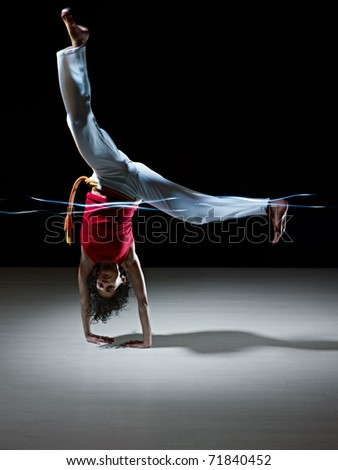 young adult latin american female handstanding and doing capoeira kick in gym, with streaks of led lights on waist. Vertical shape, full length, front view, copy space
