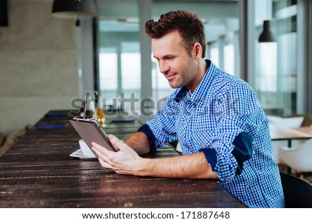Young adult looking at his tablet in a cafe - stock photo