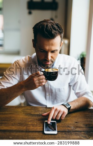 Young adult male browsing internet on smartphone and drinking coffee at restaurant - stock photo