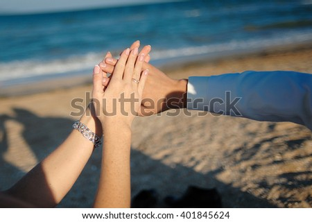 Young adult male groom and female bride holding hands on beach - stock photo
