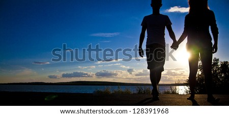 Young adult male groom and female bride holding hands on beach at sunset. Space for inscription and background - stock photo
