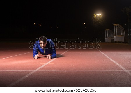 Young adult man, athlete plank exercise, night. Red running tracks.