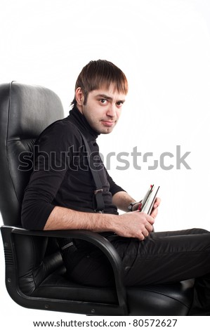 young adult man belonging to the Caucasoid race, wearing a black sweater sits in a leather director's  chair with a notepad and thinks isolated over white image,office work,clerc in chair