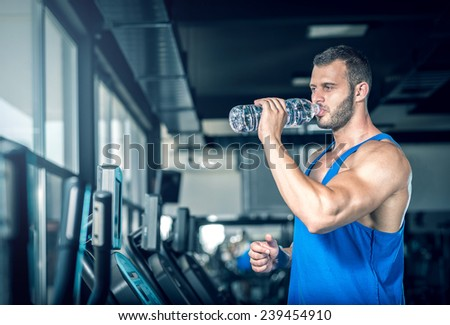 Young adult man drinking bottle of water on trreadmill in gym. - stock photo