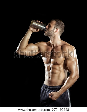 Young adult man drinking protein shake in gym. Black background. - stock photo
