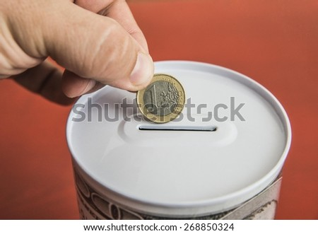 young adult man hand introducing one 1 euro coin in the slot of a moneybox against red background Sign symbol idea concept economy money ans save up No face Unrecognizable person  - stock photo