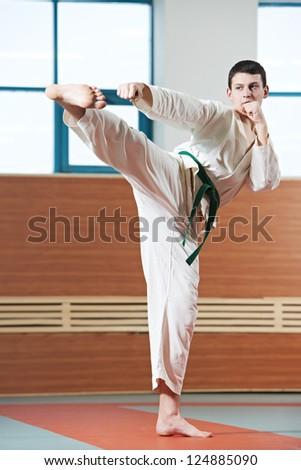 young adult man in kimono training taekwondo martial art at gym - stock photo
