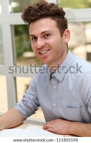 Young adult man in office with notes book