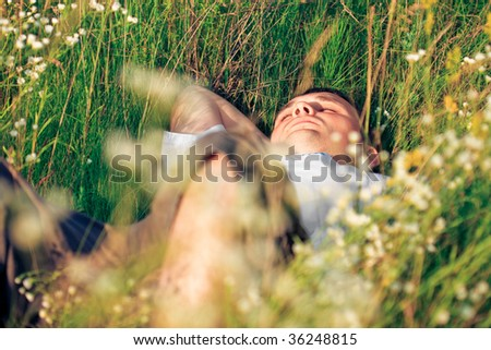 young adult man in spring grass - stock photo