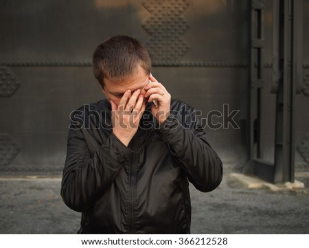 Young  adult man is devastated by bad news. Has he just lost someone ....? Dark industrial surroundings. - stock photo