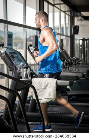 Young adult man running on treadmill in gym - stock photo