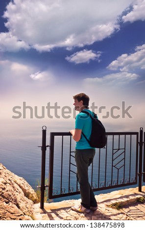 Young adult man stands on a hill and looking at the sea