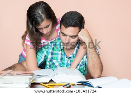 Young adult man studying at home with his daughter hugging him from behind - stock photo