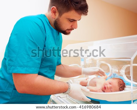 young adult man taking care of newborn baby in infant incubator - stock photo