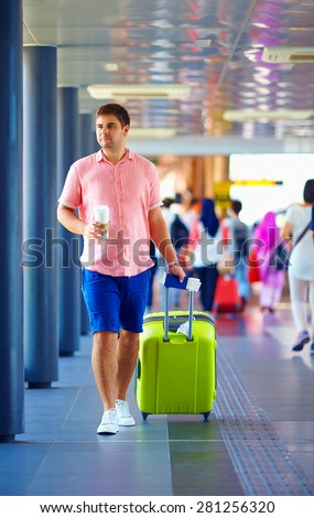young adult man walking through crowded international airport - stock photo