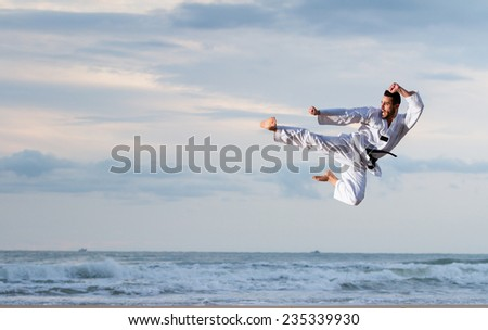 Young adult man with black belt jumping to practice Marcial Arts kick on the beach. Real shot, not a photomontage. - stock photo