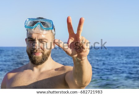 Young adult man with the beard squinting and showing a  Dubai three-finger salute on the blue sea background