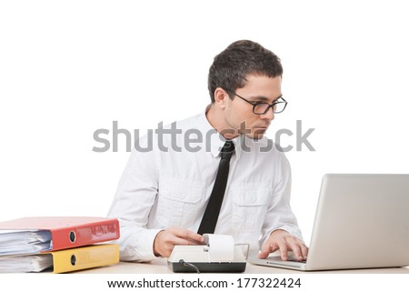 young adult man working on computer. successful manager calculating and typing on keyboard - stock photo