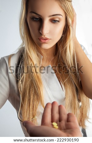 Young adult nurse taking a pills in studio - stock photo