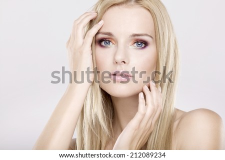 Young adult pretty woman with beautiful blond hairs and multicolor makeup on white background - stock photo