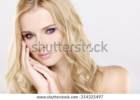Young adult pretty woman with beautiful blond hairs and multicolor makeup on white background