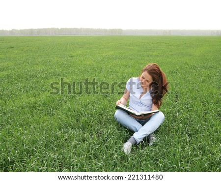 young adult redhead girl sitting on fresh spring green grass field on nature background of the setting sun, reading big book Cute woman wearing casual blue dress Empty copy space for inscription  - stock photo