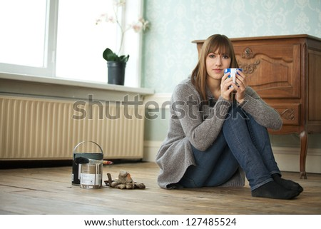 Young adult relaxing at new home with a cup of tea - stock photo
