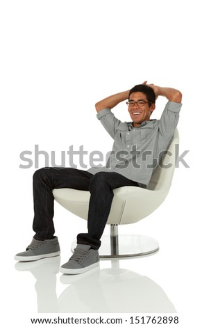 Young adult relaxing in a modern chair with hands on head