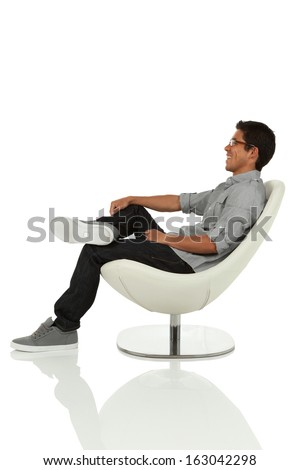 young adult sitting and leaning back on modern chair side view - stock photo