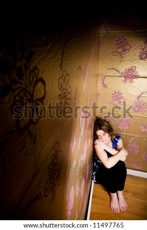 Young adult sitting on the floor feeling trapped - stock photo